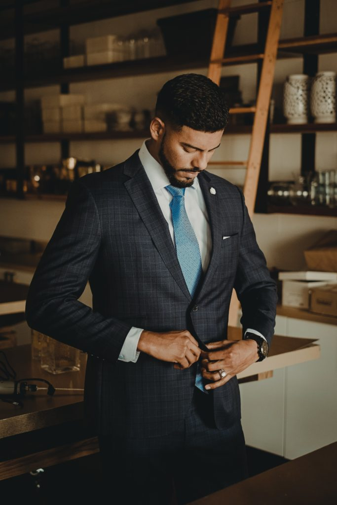 Hotel manager buttoning his two-piece suit before presenting himself in front of his department heads.